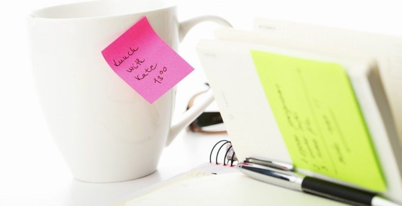 Office yellow and pink sticky note on a coffe cup